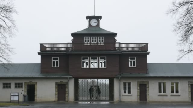people stand in front of the former main entrance to the buchenwald concentration camp on january 26 2018 near weimar germany international holocaust... - campo di concentramento di buchenwald video stock e b–roll
