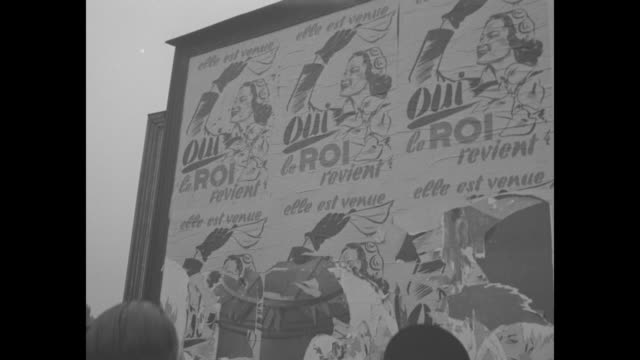 vidéos et rushes de people stand in street and look at posters in french in favor of returning king leopold iii to power / posters on wall of building / pan across... - belgique
