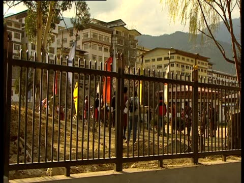 people stand near a fence in thimphu bhutan - thimphu stock videos & royalty-free footage