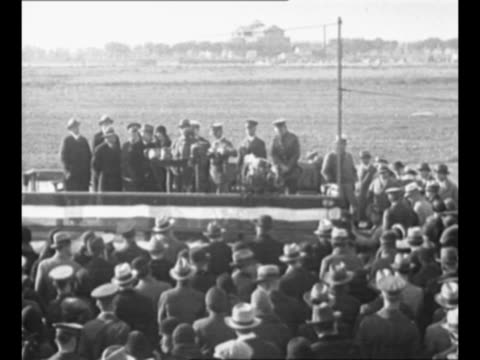 ls people stand on platform for ceremony to award capt eddie rickenbacker with the congressional medal of honor audience stands in front and airfield... - エディ リッケンバッカー点の映像素材/bロール