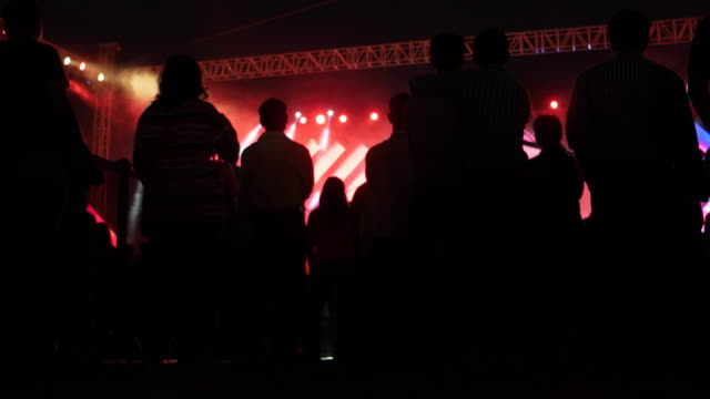 People standing and waiting in front a massive music festival stage with massive lights on trusses and a laser display