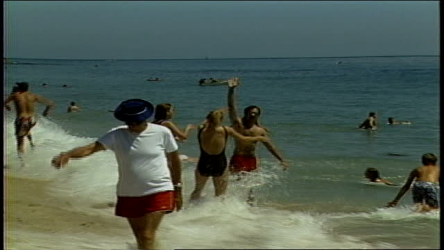 people standing at waters edge at beach - anno 1987 video stock e b–roll
