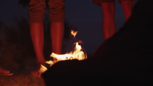 People standing by beach campfire, low angle