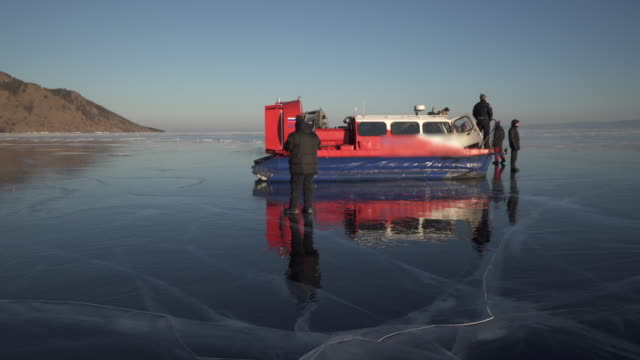 people standing by hovercraft over frozen lake baikal during winter - hovercraft stock videos & royalty-free footage