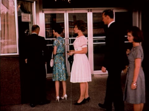 1960 MS people standing in line and purchasing tickets at theater box office / USA