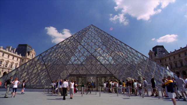 people standing in line in front of pyramide in center of courtyard of louvre / paris, france - louvre stock videos and b-roll footage