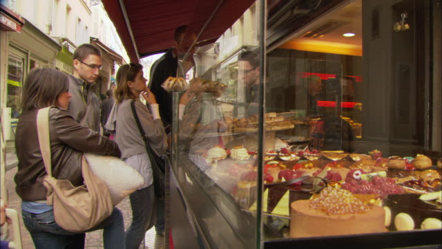ms people standing in line outside of bakery to buy pastries / paris, france - display cabinet stock videos & royalty-free footage