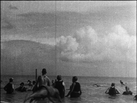 vidéos et rushes de b/w 1924 people standing in ocean as one person dives in / miami beach, florida / industrial - 1924