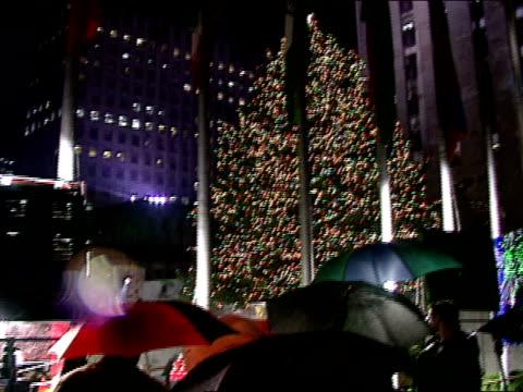 NIGHT People standing in rain w/ umbrellas behind flood lights flag poles at edge of Rockefeller Plaza LS Lighted tree