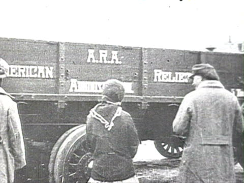 ms people standing near an american relief truck and unloading of ship audio/ russia - anno 1920 video stock e b–roll