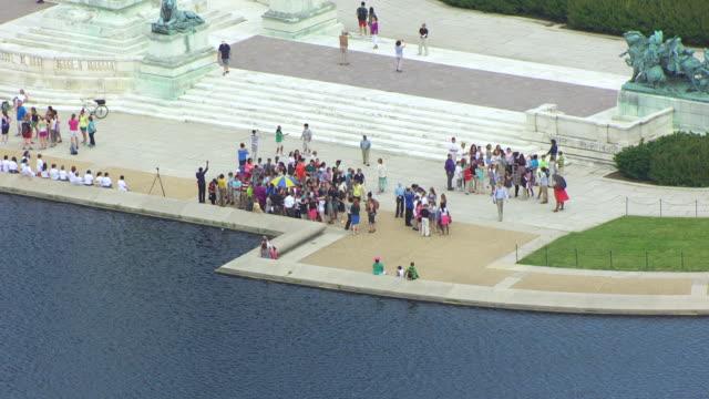 WS AERIAL POV People standing near US Capitol reflecting pool / Washington DC, United States