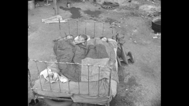 people standing next to shacks in squatters' camp / children walking along road next to shacks in squatters' camp / man walking along through trash... - dust bowl stock videos and b-roll footage
