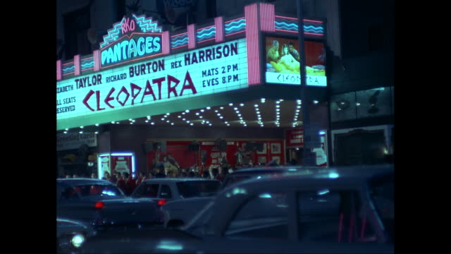 ws  people standing outside pantages theatre at night, marquee advertizing cleopatra, traffic in foreground / los angeles, california, united states - theatre banner commercial sign stock videos & royalty-free footage