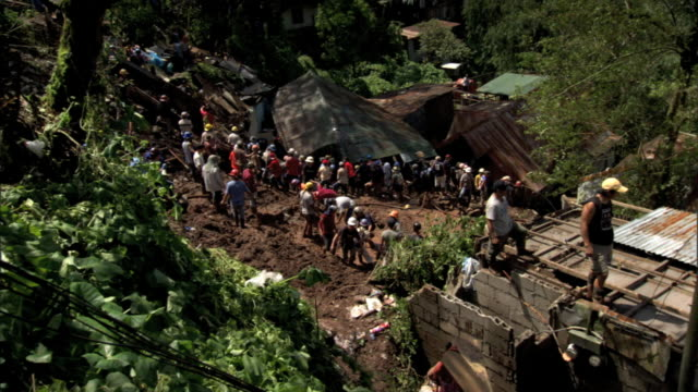people standing working by collapsed house on hillside pan to ws people working on roof of block home on right reverse pan ws people by collapsed... - luzon stock videos & royalty-free footage