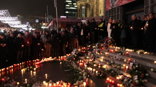 People stay with candles in their hands at the memorial to victims following its inauguration at the site of the 2016 Christmas market terror attack...