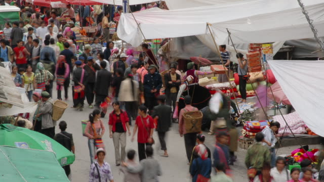people stream amongst market stalls, yunnan, china - urban road stock videos & royalty-free footage