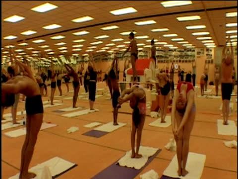 people stretching arms right back over heads during bikram yoga class - menschliche gliedmaßen stock-videos und b-roll-filmmaterial