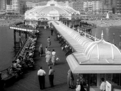 people stroll along brighton's palace pier. - ブライトン パレスピア点の映像素材/bロール