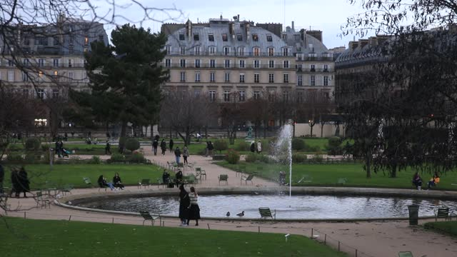 vidéos et rushes de people stroll in the jardin des tuileries on a cold and windy day, as background 'haussmann' style buildings on december 5 in paris, france. lockdown... - biomedical illustration