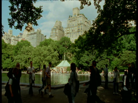 people stroll next to lake in central park, new york city - next to stock videos and b-roll footage