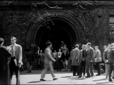 People students walking on sidewalk FG out of arched doorway of Sever Hall BG women wearing dresses men dressed in coat tie Higher education Ivy...