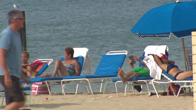 vidéos et rushes de people sun tanning on beach at north avenue beach on august 27 2013 in chicago illinois - bain de soleil
