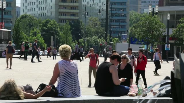People sunbathe in Alexanderplatz square as a tram passes by in the background in Berlin Germany on Wednesday May 21 People sit by a water fountain...