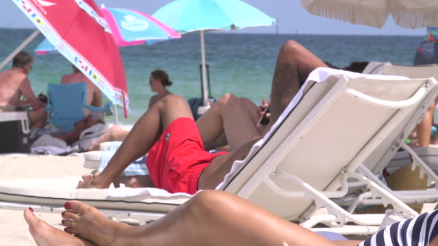 People sunbathing and looking at the phone at the Miami beach