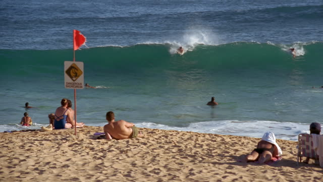 people sunbathing by dangerous shorebreak sign at sandy beach watching bodyboarders ride shorebreak / south shore, oahu, hawaii - oahu bildbanksvideor och videomaterial från bakom kulisserna