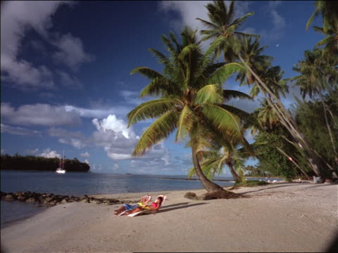 2 people sunbathing on beach in tahiti - südpazifik stock-videos und b-roll-filmmaterial