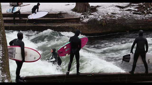 people surf at the eisbachwelle in the englischer garten during a snowfall amid the coronavirus pandemic in munich on january 14th 2021. from monday... - ミュンヘン エングリッシャーガルテン点の映像素材/bロール