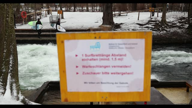 people surf at the eisbachwelle near a sign saying to keep the distance in the englischer garten during a snowfall amid the coronavirus pandemic in... - ミュンヘン エングリッシャーガルテン点の映像素材/bロール