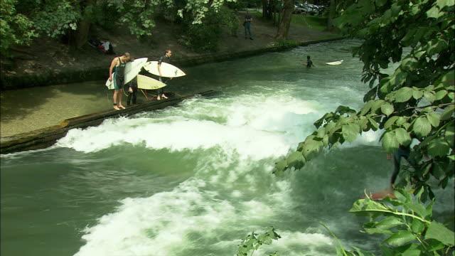 ms ha people surfing on eisbach river in englischer garten (english garden), munich, bavaria, germany - ミュンヘン エングリッシャーガルテン点の映像素材/bロール