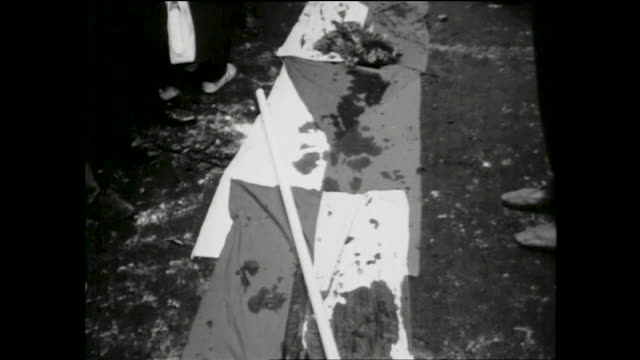 people surrounding czech flags laid on the ground with flowers and blood on top during the soviet invasion of czechoslovakia; close up views of the... - prague stock videos & royalty-free footage
