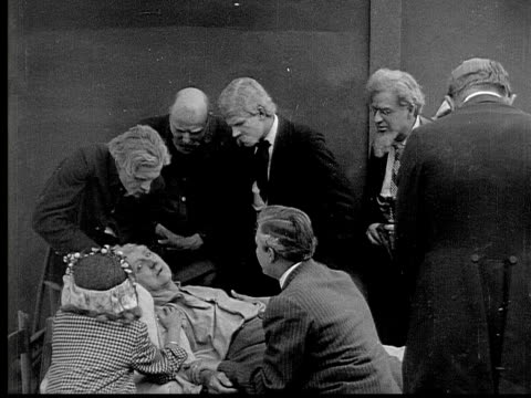 1913 b&w ms people surrounding older man on his deathbed as he points dramatically into the air - grey jacket stock videos and b-roll footage