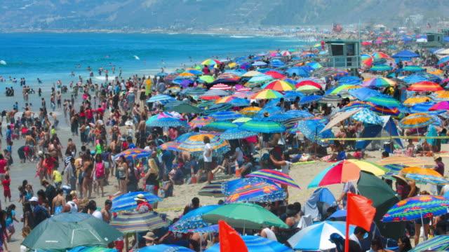 People swim in the Pacific Ocean in Santa Monica Beach, Los Angeles, California, 4K, RAW