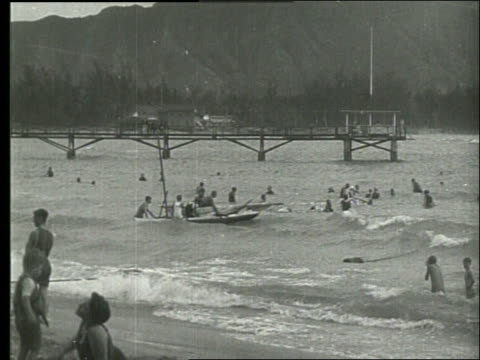 b/w people swimming and taking out sailboat in ocean / 1919 hawaii / no sound - pazifikinseln stock-videos und b-roll-filmmaterial