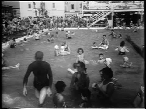 b/w 1953 people swimming in crowded swimming pool / newsreel - piscina pubblica all'aperto video stock e b–roll