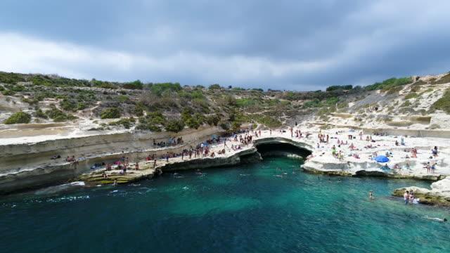 vidéos et rushes de people swimming in st.peter's pool, marsaxlokk, malta - tourism