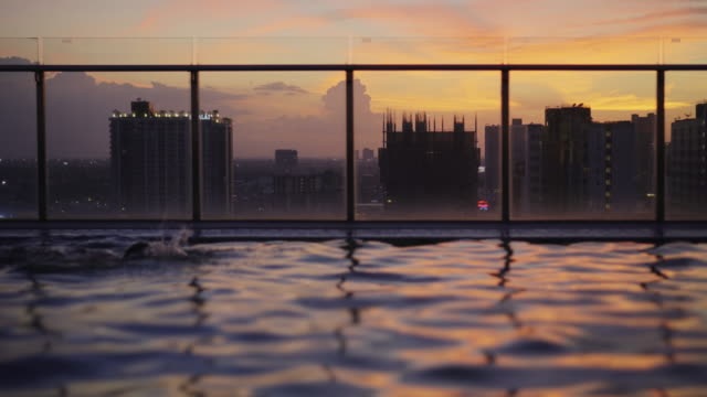 people swimming in the rooftop pool. - roof stock videos & royalty-free footage
