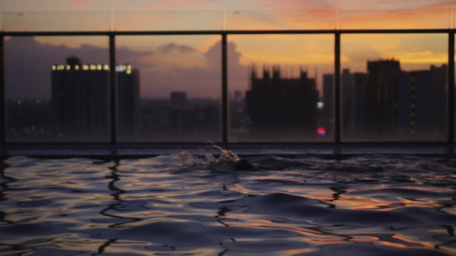people swimming in the rooftop pool,slow motion - poolside stock videos & royalty-free footage