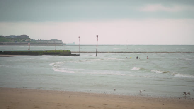 ws people swimming on margate seafront - overcast stock videos & royalty-free footage