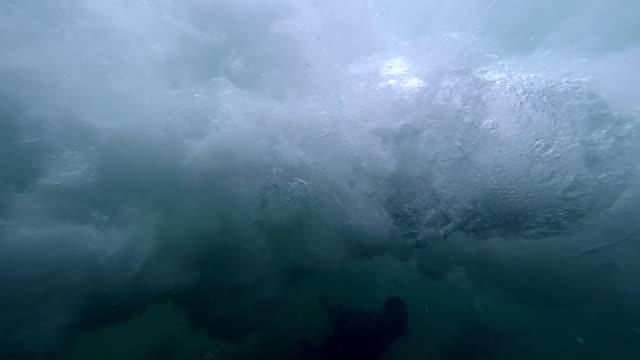 vídeos de stock, filmes e b-roll de people swimming under a breaking wave - tubo de ondas
