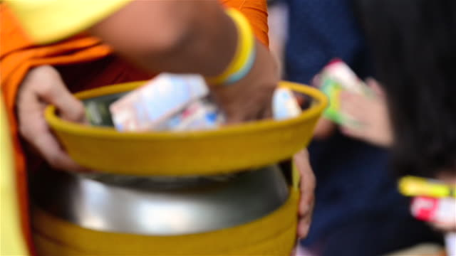 people tak bat or give alm to monks by placing foods on the lid of alm bowl - alm stock-videos und b-roll-filmmaterial