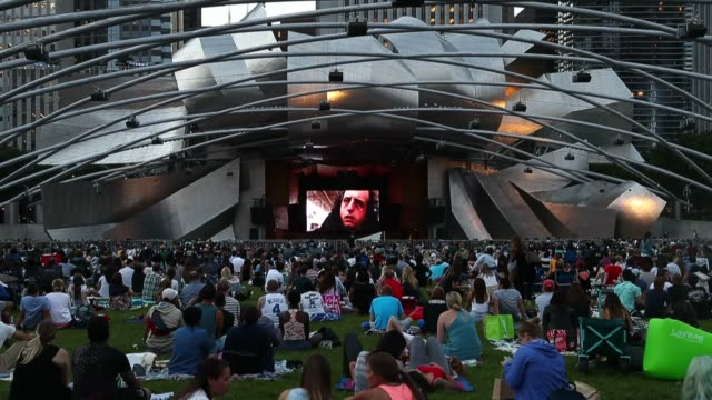 vídeos de stock e filmes b-roll de people take a seat at the jay pritzker pavilion and lounge on the great lawn at millennium park for full moon double feature ghost and the shining as... - pavilhão jay pritzker