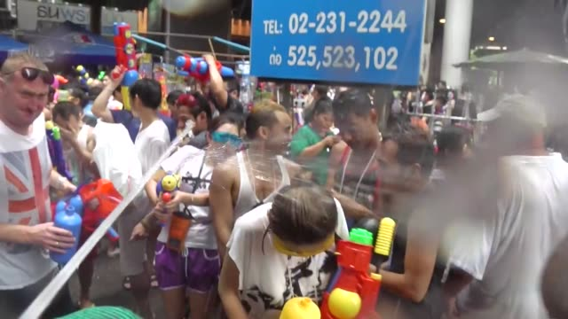 people take part in water battles to celebrate the songkran festival for the thai new year on silom road in bangkok / the songkran festival runs from... - 水鉄砲点の映像素材/bロール