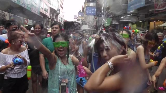 people take part in water battles to celebrate the songkran festival for the thai new year on silom road in bangkok / the songkran festival runs from... - 参加者点の映像素材/bロール
