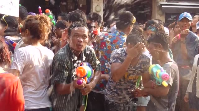 People take part in water battles to celebrate the Songkran Festival for the Thai New Year at Khao San road in Bangkok / the Songkran Festival runs...