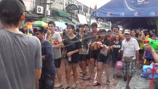 people take part in water battles to celebrate the songkran festival for the thai new year at khao san road in bangkok / the songkran festival runs... - 水鉄砲点の映像素材/bロール