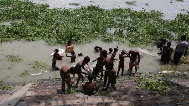 stockvideo's en b-roll-footage met people taking bath in the river buriganga in dhaka bangladesh on august 12 2018 - human interest